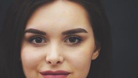 Skönhetmodellen är en kvinna med rakt långt brunt hår Sunt h?r och h?rlig yrkesm?ssig makeup Röda kanter och öga arkivfilmer