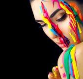 Skönhetmodellflicka med färgrik målarfärg på hennes framsida Stående av den härliga kvinnan med målarfärg för flödande flytande royaltyfri fotografi