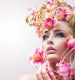 Skönhetmodellflicka med härliga blommor i hennes hår royaltyfri foto