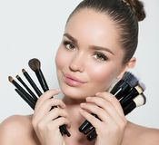 Skönhetmodellflicka, uppsättning för innehav för makeupkonstnär av sminkborstar och le Ung kvinna för härlig brunett med perfekt  royaltyfria bilder