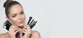 Skönhetmodellflicka, uppsättning för innehav för makeupkonstnär av sminkborstar och le Ung kvinna för härlig brunett med perfekt  arkivbilder