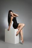skönhetmodestående av den härliga unga flickan i en svart klänning I studion på en vit kub fotografering för bildbyråer