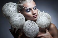Skönhetmodestående av en härlig kvinna med idérik makeup på hennes framsida Vita flätade bollar runt om huvudet av modellen royaltyfria bilder