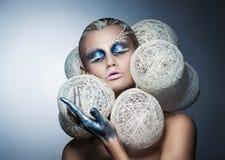 Skönhetmodestående av en härlig kvinna med idérik makeup på hennes framsida Vita flätade bollar runt om huvudet av modellen royaltyfria foton