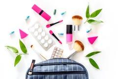 Skönhetpåse med skönhetsmedel, preventivmedel och preventivpillerar på bästa sikt för vit tabellbakgrund Fotografering för Bildbyråer
