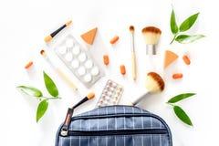 Skönhetpåse med skönhetsmedel, preventivmedel och preventivpillerar på bästa sikt för vit tabellbakgrund Arkivfoton