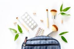 Skönhetpåse med skönhetsmedel, preventivmedel och preventivpillerar på vit copyspace för bästa sikt för tabellbakgrund Royaltyfri Bild