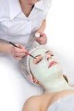 Skönhetsalong, applicera för maskering för ögon ansikts- Arkivbild