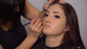 Skönhetsalong Den unga härliga flickamodellen sitter i stolen Makeupkonstnären gör flickamakeup Brunett i en skönhet stock video
