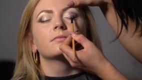Skönhetsalong Den unga härliga flickamodellen sitter i stolen Makeupkonstnären gör flickamakeup Makeupkonstnär stock video