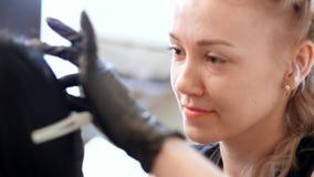 Skönhetsalong en stående av en förlage, en cosmetologist, i svarta rubber handskar, arbetar med en klient, älskar hennes arbetar  stock video