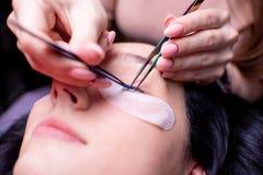 Skönhetsalong, slut för ögonfransförlängningstillvägagångssätt upp lång kvinna för härligt hår arkivfoto