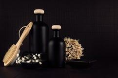 Skönhetsmedel förlöjligar upp - tomma svarta flaskor, badtillbehör, vita blommor på det mörka wood brädet, kopieringsutrymme Royaltyfri Fotografi