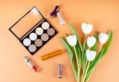 Skönhetsmedel- och blommalögner på en mjuk persikabakgrund Innehåll av kvinnors kosmetiska påse royaltyfri fotografi