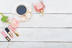 Skönhetsmedel och en kopp kaffe med macaron på en vit träbac Royaltyfri Bild