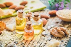 Skönhetsmedel och läkarundersökningolja av valnötter, mandlar, närbild för kakaosmör royaltyfri fotografi
