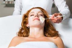 Skönhetsmedel och skönhet - applicera den ansikts- maskeringen Arkivfoto