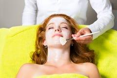 Skönhetsmedel och skönhet - applicera den ansikts- maskeringen Fotografering för Bildbyråer