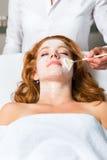 Skönhetsmedel och skönhet - applicera den ansikts- maskeringen Arkivbilder