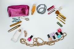 Skönhetsmedel, smycken, dofter och en härlig rosa kosmetisk påse på en vit bakgrund, bästa sikt arkivbilder