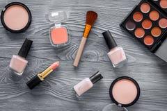 Skönhetsmedel ställer in med beiga, och nakenstudie tonar för naturlig makeup på bästa sikt för grå träbakgrund Arkivfoton