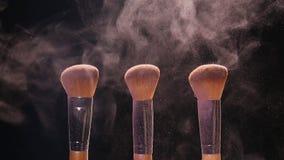 Skönhetsmedelborstar och färgrikt makeuppulver för explosion arkivfilmer