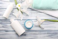 Skönhetsmedelkräm i den glass kruset med handdukar och härliga blommor på royaltyfri foto