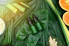 Skönhetsmedelskincare med vitamin-cextrakten, kosmetiska flaskbehållare med nya apelsinskivor, tom etikett för att brännmärka mod arkivbild