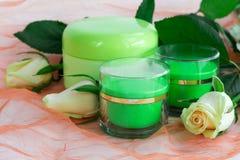 Skönhetsmedeluppsättning av krämflaskor med rosor Arkivbild