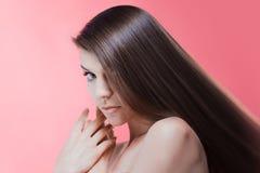 Skönhetstående av brunetten med perfekt hår, på en rosa bakgrund Den unga asiatiska flickan som kammar hår med, fingrar isolerat  Fotografering för Bildbyråer