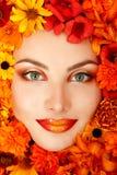 Skönhetstående av den härliga kvinnliga framsidan med orange blommor Arkivbild