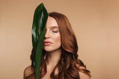 Skönhetstående av den sinnliga ljust rödbrun kvinnan med långt hår royaltyfri bild