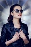 Sk?nhetst?ende av den stilfulla unga kvinnan i l?deromslaget och solglas?gon som bort som ser isoleras p? en silverbakgrund royaltyfri bild