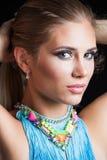 Skönhetstående av den unga blonda kvinnan med den blåa halsbandstudion Royaltyfri Bild