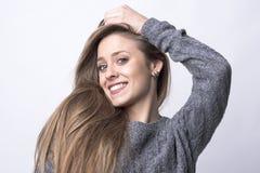 Skönhetstående av den unga gulliga kvinnan med långt sunt hår som poserar och ler fotografering för bildbyråer