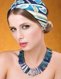 Skönhetstående av den unga härliga kvinnan med sinnlig blick Halsband och hår med en sjalett Arkivbild