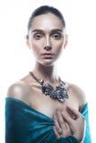 Skönhetstående av den unga kvinnan med en exakt frisyr och prydnaden på en hals som isoleras på en vit bakgrund royaltyfri bild