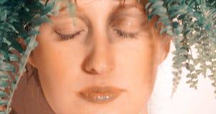 Skönhetstående av den unga kvinnan med gröna ormbunkesidor stock video