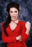 Skönhetstående av en härlig sexig brunett i en röd klänning på en grå bakgrund fotografering för bildbyråer