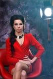 Skönhetstående av en härlig sexig brunett i en röd klänning på en grå bakgrund royaltyfri fotografi