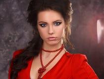Skönhetstående av en härlig sexig brunett i en röd klänning på en grå bakgrund royaltyfria foton