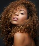 Skönhetstående av en kvinnlig modemodell med lockigt hår Arkivbild