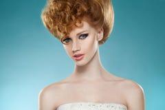 Skönhetstående av en röd hairred flicka med hairdressed och stänk, med nakna skuldror som isoleras på en blå bakgrund fotografering för bildbyråer