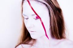 Skönhetstående av flickan med den vita framsidan med det röda bandet Royaltyfri Fotografi