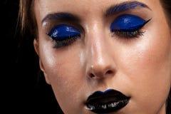 Skönhetståenden av bärande blått för kvinnan utgör med svarta kanter Arkivfoto