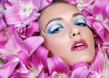 Skönhetståenden av den stiliga europeiska flickan i liljor blommar Arkivbilder