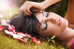 Skönhetståenden av kvinnan med blommakronblad nära vänder mot fotografering för bildbyråer