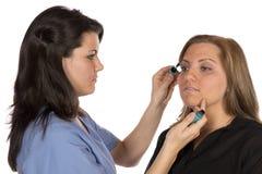 Skönhettekniker som applicerar makeup på klient Arkivfoton