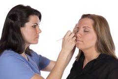 Skönhettekniker som applicerar makeup på klient Royaltyfria Foton