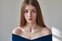 Skönhettema: stående av en härlig ung flicka med fräknar på henne framsida och bära en blå klänning på en vit bakgrund i studi fotografering för bildbyråer